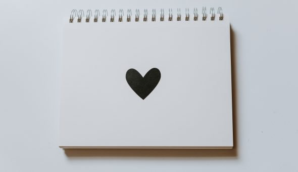 Image of a black heart on a blank notebook.