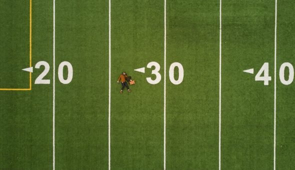 "someone laying on a sports ground which has marks of ""20"", ""30"", ""40""."