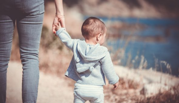 Photo of parent holding a child's hand.