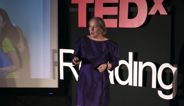 Dr Olivarius speaking on stage at TEDxReading, with slide prompts in the background.