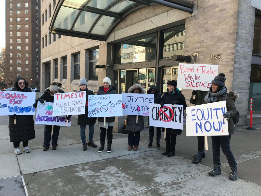 """Protesters outside the Icahn School of Medicine, holding signs saying """"justice for women"""" """"equity now""""."""