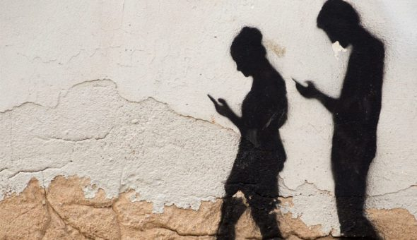 Image of shadows of two people on wall. They are looking at their phones while walking.