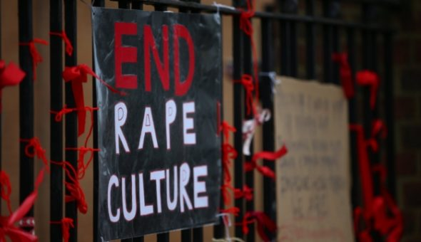 Photo of protest banner attached to metal fence saying 'End Rape Culture'.