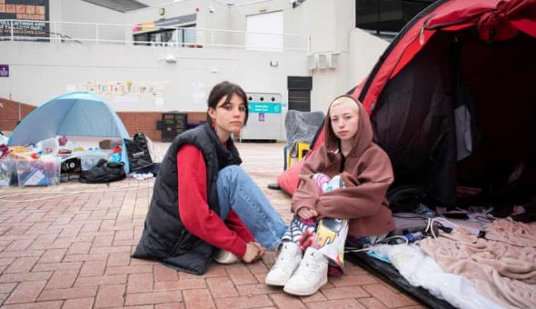 Photo of two female students sitting by tents as part of the sit-in at the University of Warwick.