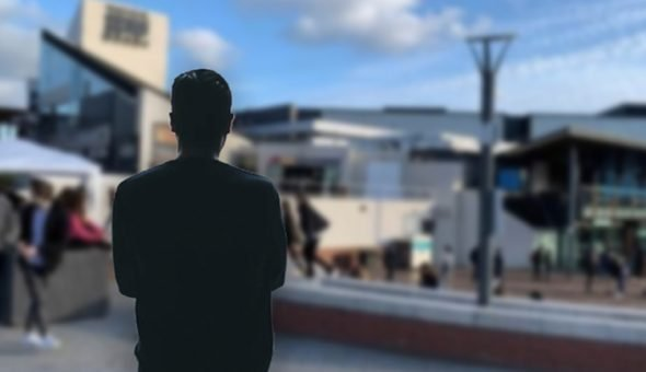 Photo of a man looking at a building with his back facing the camera.