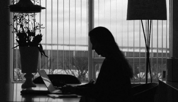 Woman working in office on laptop.